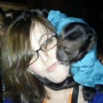 Monkey sits on the shoulder of a person while kissing her cheek.