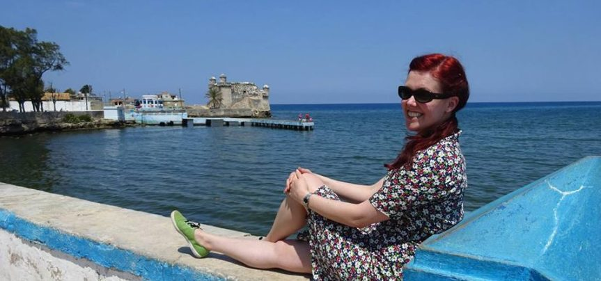 Person sits with legs crossed on a wall that overlooks a bay.