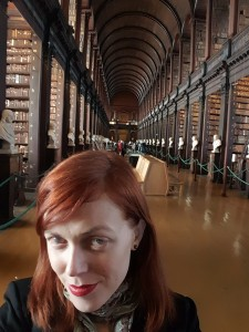 Person stands in front of a long hall that has a vaulted Cathedral ceiling and is lined with rows of books.