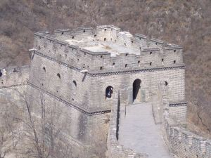 Person sits inside the window of a square stone structure at a juncture of the Great Wall.